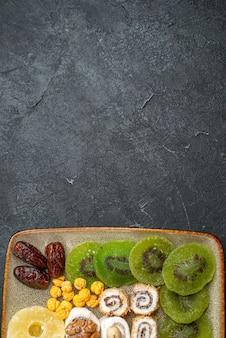 Draufsicht geschnittene getrocknete früchte ananasringe und kiwis auf grauem schreibtisch trockenfrucht rosinen süß-sauer vitamin gesundheit