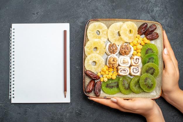 Draufsicht geschnittene getrocknete früchte ananasringe und kiwis mit walnüssen auf grauem schreibtisch trockenfrüchte rosinen süßes vitamin gesundheit