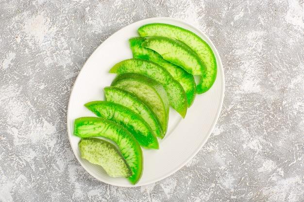 Draufsicht geschnittene grüne gurken innerhalb platte auf weißer oberfläche
