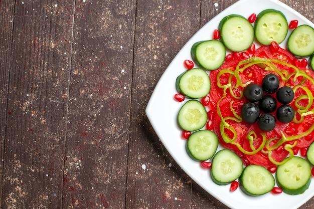 Draufsicht geschnittene gurken mit oliven innerhalb platte auf einem braunen rustikalen schreibtisch diät salat gemüse gemüse vitamin gesundheit