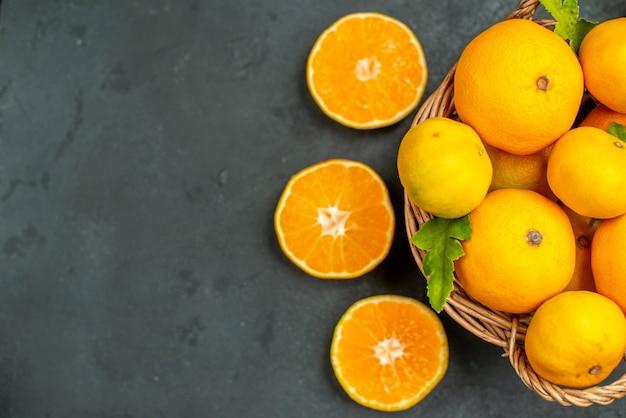 Draufsicht geschnittene orangen mandarinen und orangen im weidenkorb auf dunklem hintergrund