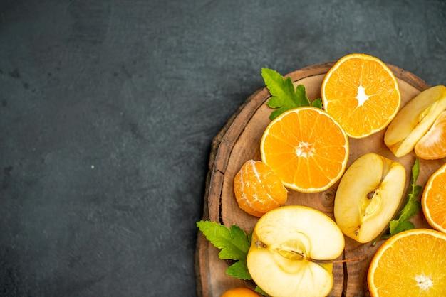 Draufsicht geschnittene orangen und äpfel geschnittene orange auf dunkler oberfläche