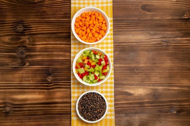 Draufsicht geschnittene paprika mit gewürzen auf dem braunen holztisch gemüsemehl lebensmittelgesundheitssalat