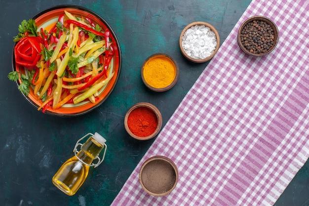 Draufsicht geschnittene paprika mit olivenöl und gewürzen auf dunklem schreibtisch