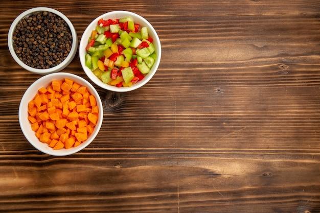 Draufsicht geschnittene paprika mit verschiedenen gewürzen auf dem braunen holztisch gemüsemehl lebensmittelgesundheitssalat