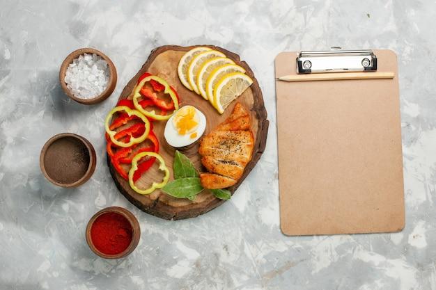 Draufsicht geschnittene paprika mit zitronengewürzen und brötchen auf weißem schreibtisch