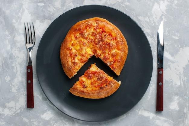 Draufsicht geschnittene pizza mit käse auf weißem schreibtisch