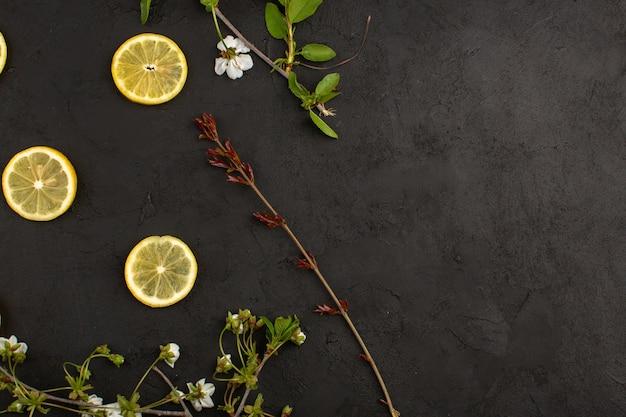 Draufsicht geschnittene zitronensauer frisch zusammen mit weißen blumen auf dem dunklen hintergrund