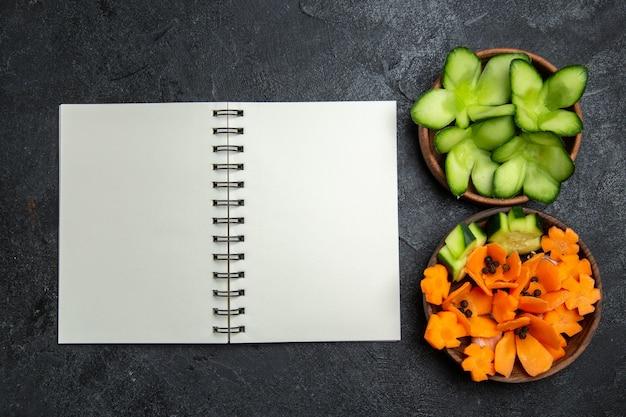 Draufsicht geschnittener entworfener salat mit notizblock auf grauem hintergrundsalatgesundheitsnahrungsdiätgemüse