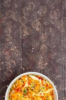 Draufsicht geschnittener gemüsesalat frisch und gesalzen innerhalb platte auf dem braunen hölzernen hintergrundgemüsemahlzeitgericht frisches foto