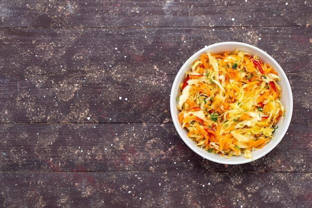 Draufsicht geschnittener gemüsesalat frisch und gesalzen innerhalb platte auf dem braunen schreibtisch gemüselebensmittelgericht frisches foto