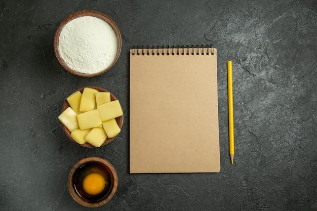 Draufsicht geschnittener käse mit mehl und notizblock auf grauem hintergrundteigmehl-rohkostauflauf