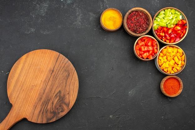 Draufsicht geschnittener pfeffer mit gewürzen auf grauem hintergrundmahlzeitsalatgesundheitsgemüse würzig