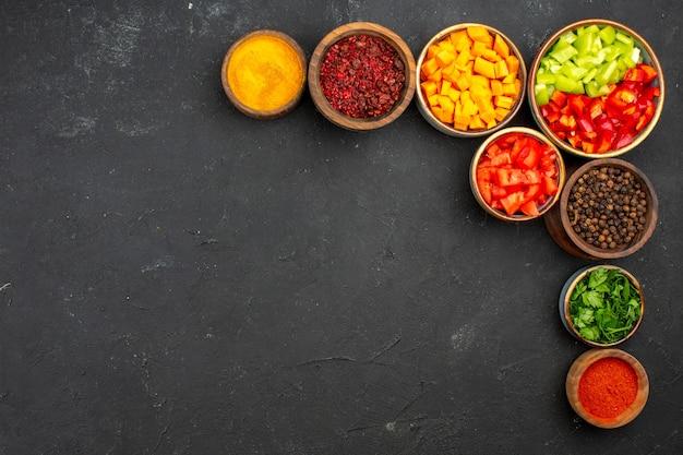 Draufsicht geschnittener pfeffer mit verschiedenen gewürzen auf dem grauen hintergrundmahlzeitsalatgesundheitsgemüse würzig