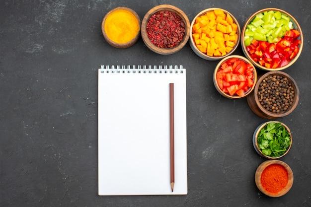 Draufsicht geschnittener pfeffer mit verschiedenen gewürzen auf grauem hintergrundmahlzeitsalatgesundheitsgemüse scharf