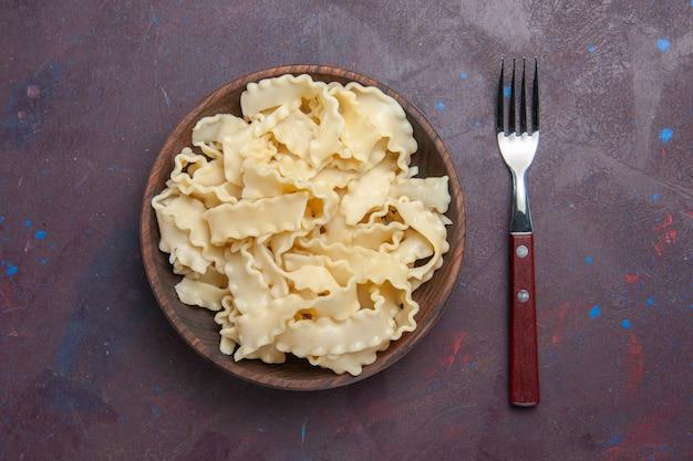 Draufsicht geschnittener roher teig innerhalb brauner platte auf dem dunklen hintergrundmahlzeitnahrungsmittelessen-nudelteig