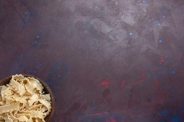 Draufsicht geschnittener roher teig innerhalb der braunen platte auf dunklem hintergrundmahlzeitteignudeldinner