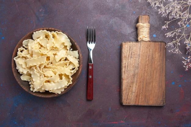 Draufsicht geschnittener roher teig innerhalb der braunen platte auf dunklem schreibtischmahlzeitnahrungsmittelessen-nudelteig