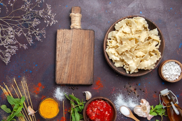 Draufsicht geschnittener roher teig mit gewürzen auf einem dunklen hintergrundteignudelnahrungsmittel-abendessenmahlzeit Kostenlose Fotos