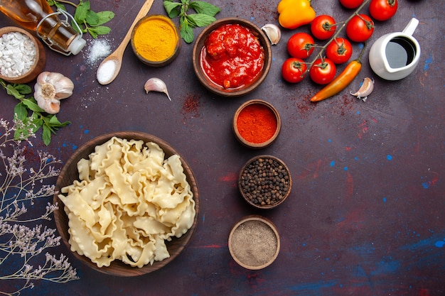 Draufsicht geschnittener roher teig mit roten tomaten und verschiedenen gewürzen auf dunklem hintergrund teignudelmahlzeit-lebensmittelgemüse