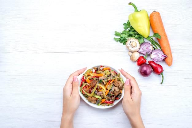 Draufsicht geschnittenes fleischgericht mit gekochtem gemüse zusammen mit frischem gemüse auf dem leichten schreibtisch essen mahlzeit gericht fleisch