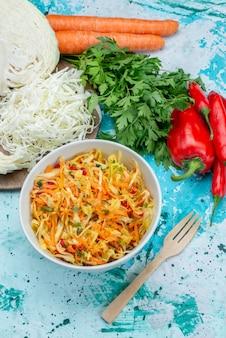 Draufsicht geschnittenes frisches gemüse langer und dünner zusammengesetzter salat innerhalb platte mit grünkohlpaprika auf dem hellblauen schreibtischnahrungsmittelmahlzeit-gemüsesalat