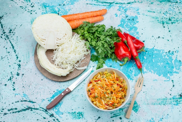 Draufsicht geschnittenes frisches gemüse langer und dünner zusammengesetzter salat innerhalb platte mit grünkohlpaprika auf der hellblauen oberfläche lebensmittel mahlzeit gemüse mittagessen gesunden salat