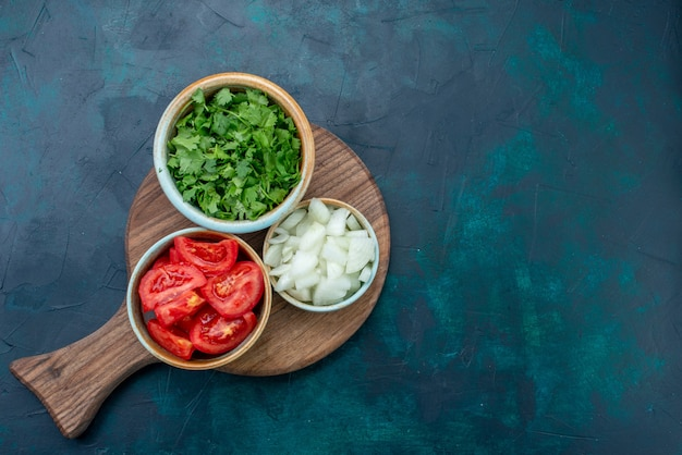 Draufsicht geschnittenes frisches gemüse tomaten und zwiebeln mit gemüse auf dunkelblauem schreibtisch essen abendessen mahlzeit gemüsegericht