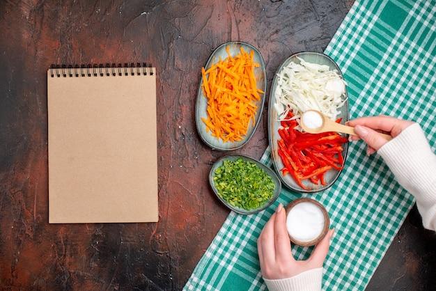 Draufsicht geschnittenes gemüse karottenkohl und paprika mit grüns auf dunklem tisch