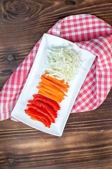 Draufsicht geschnittenes gemüse karottenpaprika und kohl auf brauner oberfläche
