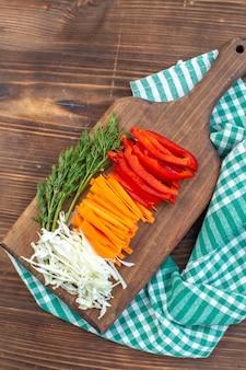 Draufsicht geschnittenes gemüse kohl karottengrün und pfeffer auf schneidebrett braune oberfläche