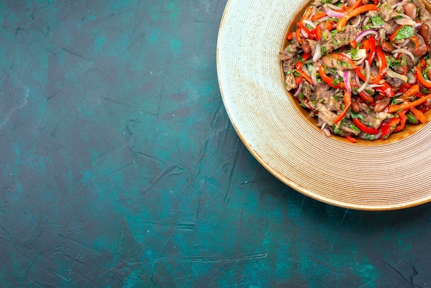 Draufsicht geschnittenes gemüse mit fleisch, das einen salat innerhalb platte auf dem dunklen hintergrund gemüsesalat fleisch essen mahlzeit macht