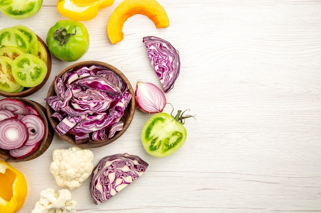 Draufsicht geschnittenes gemüse rotkohlgrüner tomatenkürbis rote zwiebel paprika blumenkohl zitrone in holzschalen auf weißer holzoberfläche freiraum
