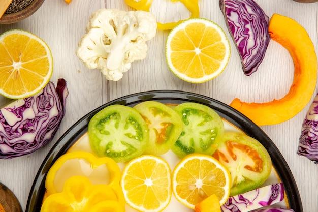 Draufsicht geschnittenes gemüse und obst kürbis persimone rotkohl zitronengrüne tomaten gelbe paprika auf schwarzer platte auf weißem tisch
