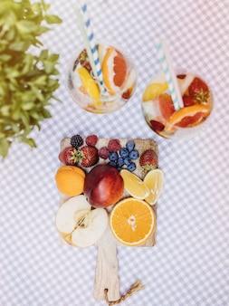 Draufsicht geschnittenes obst auf schneidebrett und fruchtcocktails