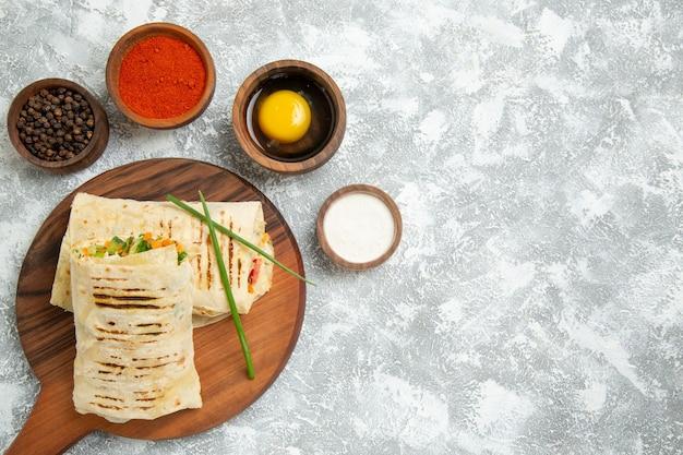 Draufsicht geschnittenes sandwich mit verschiedenen gewürzen auf weißem hintergrund brot sandwich burger essen mahlzeit brötchen