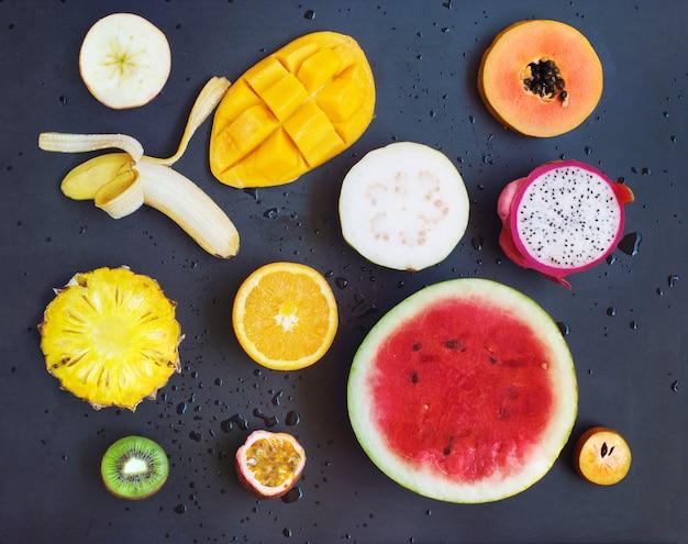 Draufsicht-gesetzter tropischer schnitt trägt schwarzen hintergrund früchte