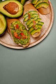 Draufsicht gesunde avocado-toasts auf holzplatte.