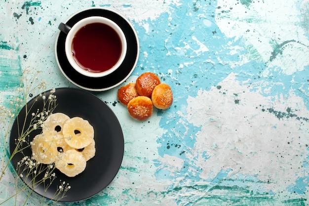 Draufsicht getrocknete ananasringe in der platte mit kuchen und tasse tee auf blauem hintergrund früchte ananas trockener süßer zucker