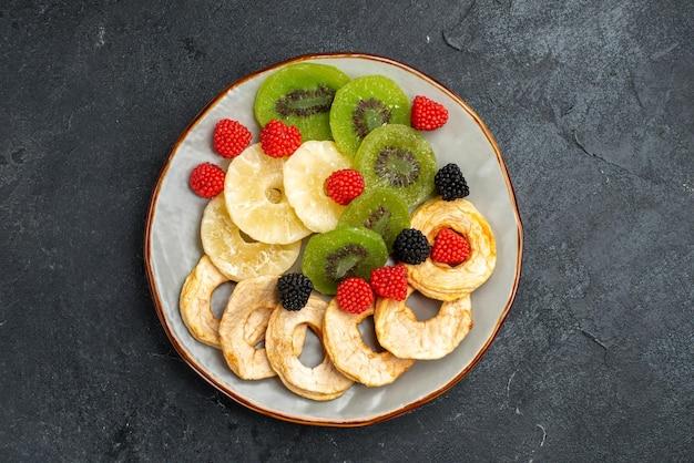 Draufsicht getrocknete ananasringe mit getrockneten kiwis und äpfeln auf der dunkelgrauen oberfläche