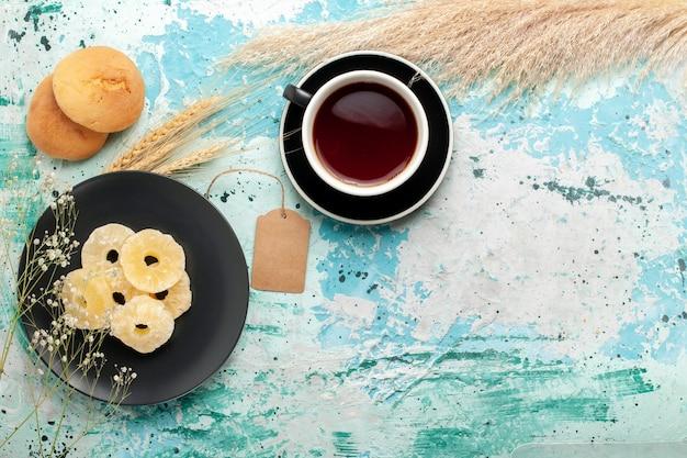 Draufsicht getrocknete ananasringe mit tasse tee auf dem blauen schreibtischkuchen backen fruchtkeks süße zuckerkekse