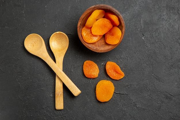 Draufsicht getrocknete aprikosenrosinen mit holzlöffeln auf dunkler oberfläche trockenfruchtrosinen