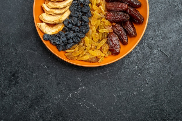 Draufsicht getrocknete früchte mit rosinen innerhalb platte auf grauem raum