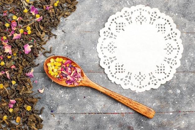 Draufsicht getrockneter frischer tee auf dem grauen hölzernen schreibtisch