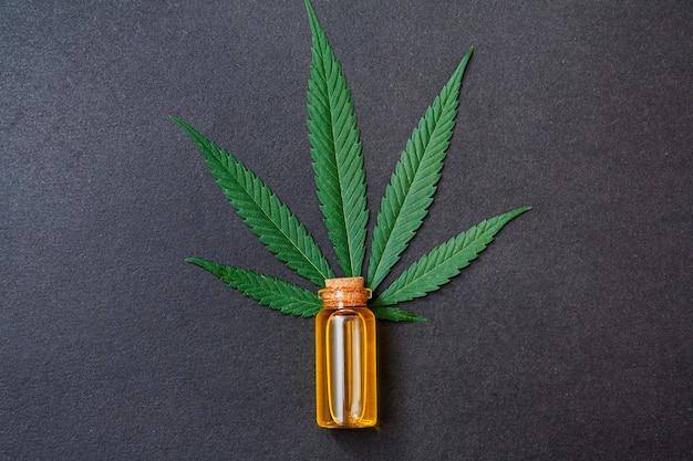 Draufsicht-glasflasche mit cannabisöl nahe pflanze auf schwarzem hintergrund