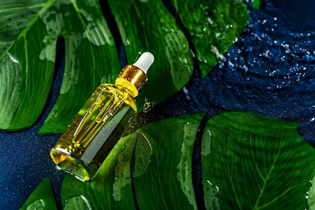 Draufsicht-glasflasche mit weißer pipette liegt auf wasser und grünen blättern auf klassischem blauem hintergrund, öko-naturkosmetikkonzept
