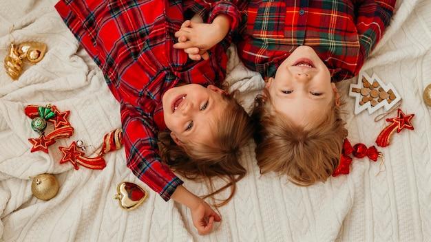 Draufsicht glückliche kinder, die spaß im bett an weihnachten haben
