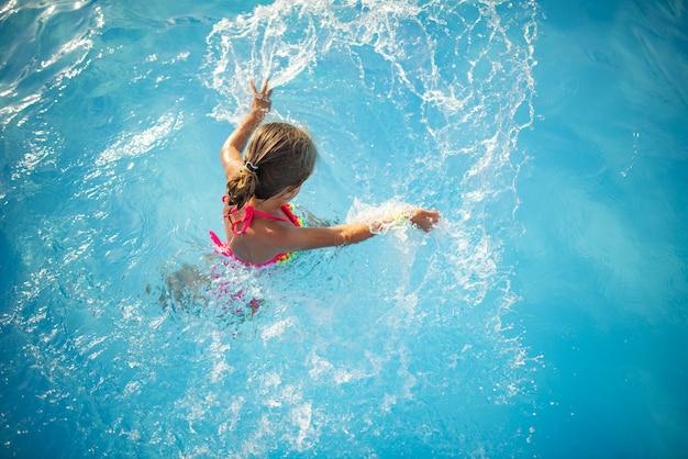 Draufsicht glückliches kleines mädchen in der hellen farbe badebekleidung schwimmt im klaren warmen pool