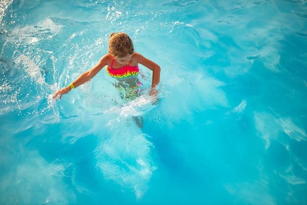 Draufsicht glückliches kleines mädchen in der hellen farbe badebekleidung schwimmt im klaren warmen poolwasser