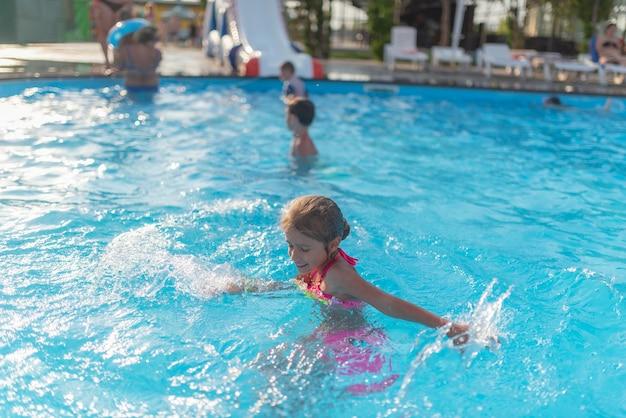 Draufsicht glückliches kleines mädchen in leuchtenden farbbadebekleidung schwimmt im klaren warmen poolwasser sonniger sommertag während des urlaubs. familienurlaub und tourismuskonzept.